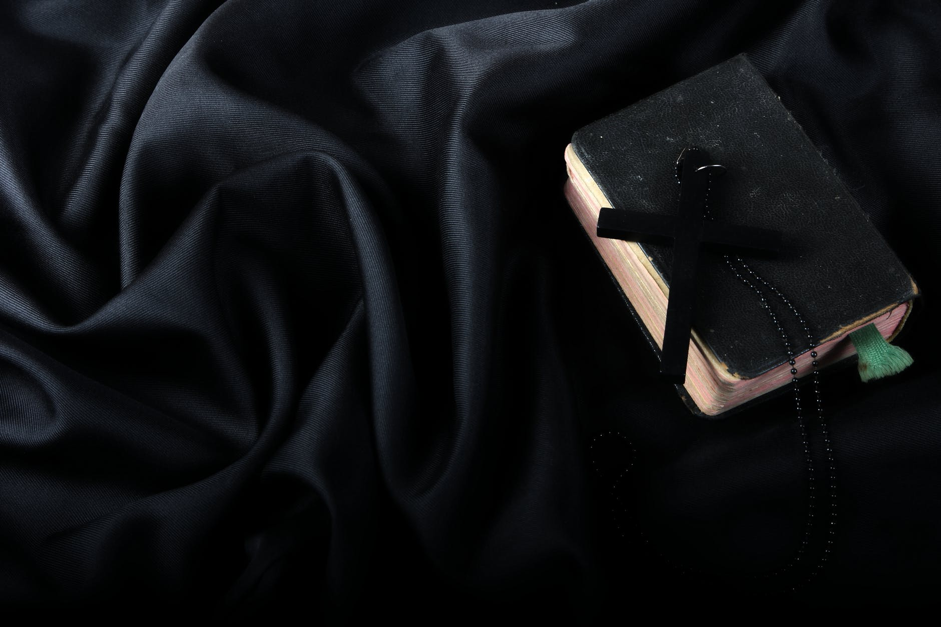 black cross on hard cover bible on top of black textile